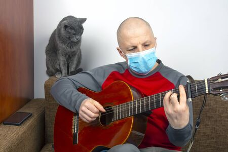 man in at home in quarantine because of an epidemic of coronavirus plays a classical guitar next to a gray cat Archivio Fotografico