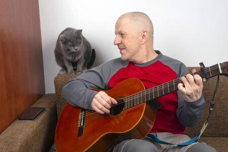 man plays the classical guitar next to a gray cat on a white background.
