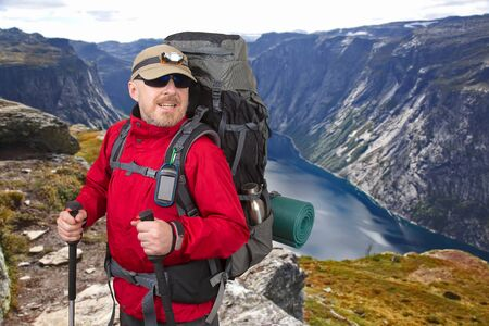 Happy tourist with backpack is traveling in the highlands. Lake in the language of the Troll. Norway