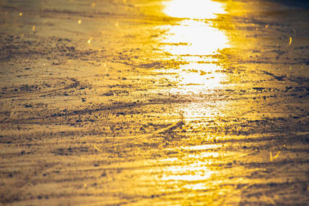 Reflection of the setting sun on the surface of the ice rink. Texture and backgrounds