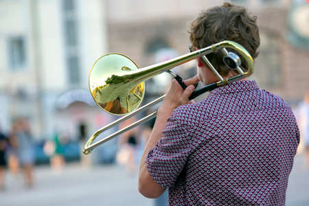 Reflection of the street in the instrument solo trumpet. male musician plays the trombone. music and creativity. jazz and blues