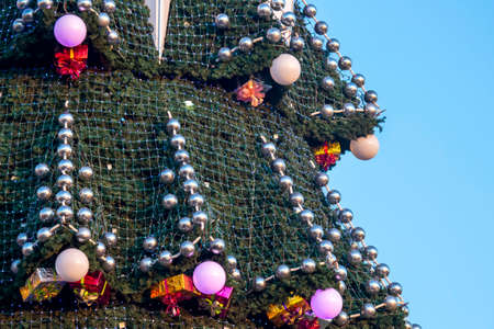 decorated Christmas tree on the background of blue sky. part of large outdoor Christmas tree closeup