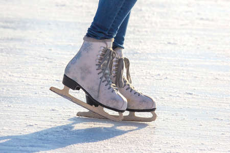 legs of a girl in blue jeans and white skates on an ice rink. hobbies and leisure. winter sports