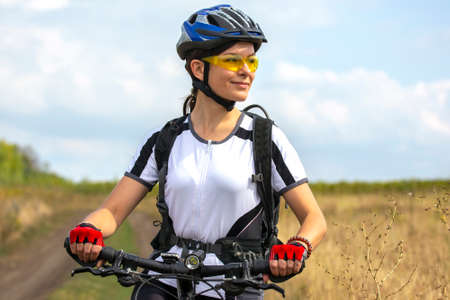 Beautiful and happy girl cyclist with a bike on nature. Healthy lifestyle and sports. Leisure and hobbies