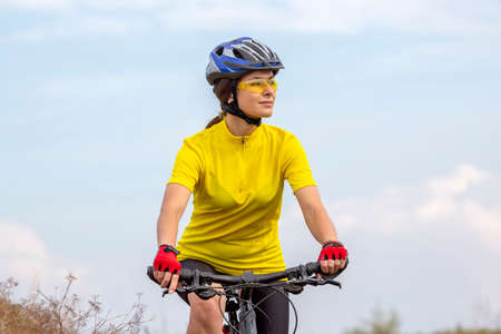 beautiful and happy girl cyclist rides a bicycle on the road in nature. Healthy lifestyle and sports. Leisure and hobbies