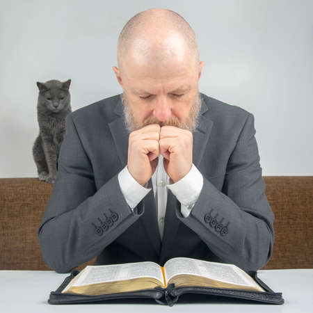 successful bearded businessman praying and Bible student