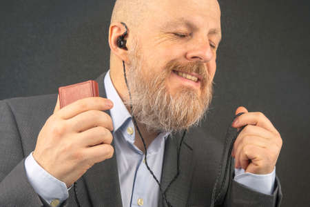 bearded business man enjoys listening to his favorite music from an audio player with small headphones. audiophile and music lover.
