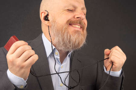 bearded business man enjoys listening to his favorite music through an audio player in small headphones. audiophile and music lover.