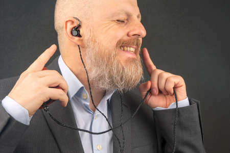 bearded business man likes to listen to his favorite music at home with an audio player in small headphones. audiophile and music lover.