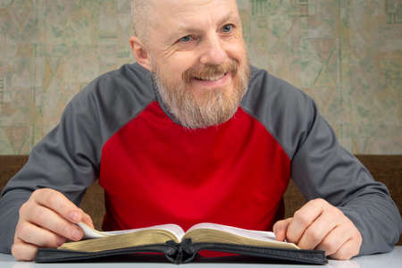 happy bearded man studying the bible