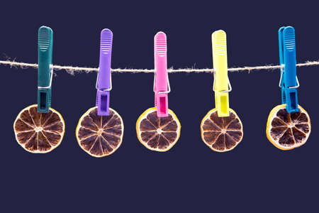 dried pieces of citrus fruits hang on clothespins