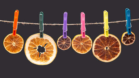Many dried pieces of different citrus fruits hang on colored clothespins