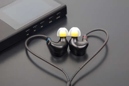 In-ear headphones for Hi-Fi music player. Audio sound and modern equipment for music lovers