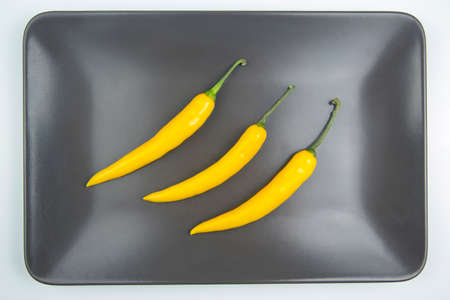 yellow hot chili on a gray background. Pepper. Vegetable vitamin food.