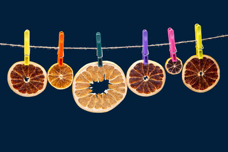 dried pieces of different citrus fruits hang on colored clothespins Reklamní fotografie