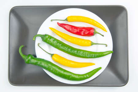 Colored hot chili on a plate. Pepper. Vegetable vitamin food.