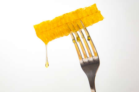 Drops of fresh honey drip from wax honey on a table fork. vitamin nutrition and bee product.