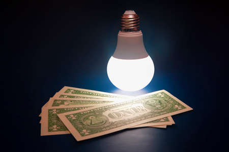 Glowing LED lamp and dollar bills on a dark background. Business and savings. Modern technology and electricity