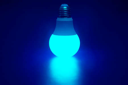 Glowing bright green LED lamp on a dark blue background. Business and savings. Modern technology and electricity