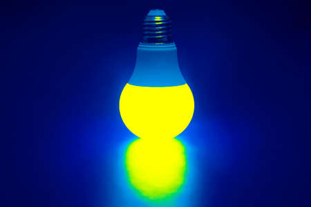 Glowing yellow LED lamp on a dark background. Business and savings. Modern technology and electricity