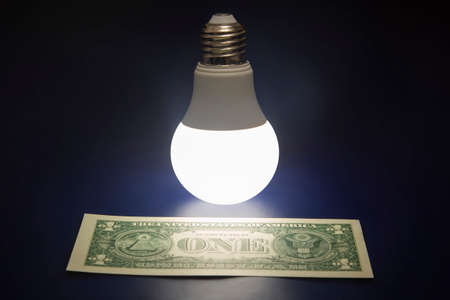 Glowing LED lamp and one dollar bill on a dark background. Business and savings. Modern technology and electricity