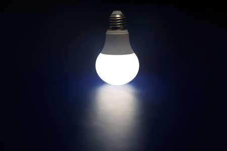 Glowing LED lamp on a dark blue background. Modern technology and electricity Zdjęcie Seryjne