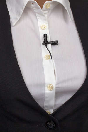 small audio microphone for voice recording with a clothespin attached to a woman's shirt.