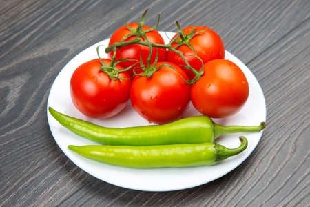 red tomatoes and green hot peppers on a kitchen board