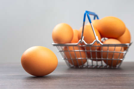 chicken eggs in a supermarket grocery basket on a wooden background. Stock Photo