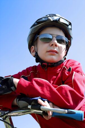 Boy on bicycle looks at end of the city