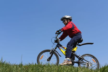 Boy on bicycle on top of the hill