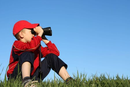 Boy looks into binoculars on top of hill