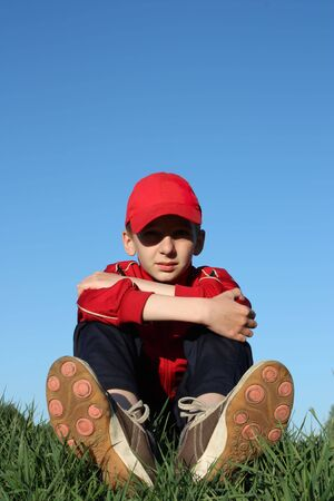 Boy sits on top of the hill