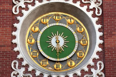 Ancient clock with gold numeral on tower