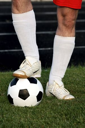 Legs of soccer player with classic soccer ball over green grass Stock Photo