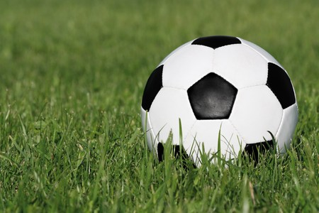Classic black and white soccer ball on green grass