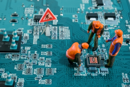 Miniature engineers fixing error on chip of motherboard. Computer repair concept. Close-up view.