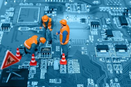 Miniatuur ingenieurs vaststelling van fouten op de chip van de printplaat. Computer reparatieconcept. Close-up. Stockfoto