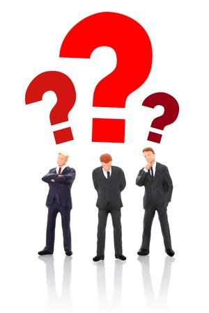 Three miniature businessman thinking - teamwork concept