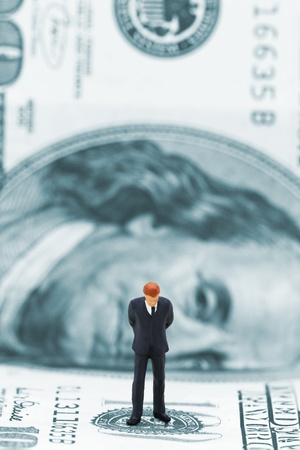 Miniature businessman thinking on dollar banknote