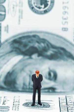 Miniature businessman thinking on dollar banknote