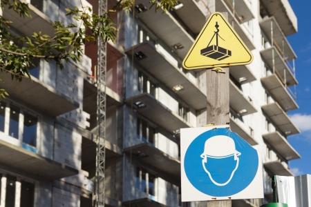 Broken sign  Hard hat area  near under construction building on background