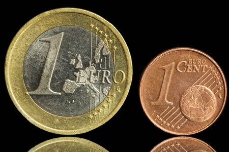 Two used coin - one euro and one eurocent - isolated on black background  Closeup view  Stock Photo