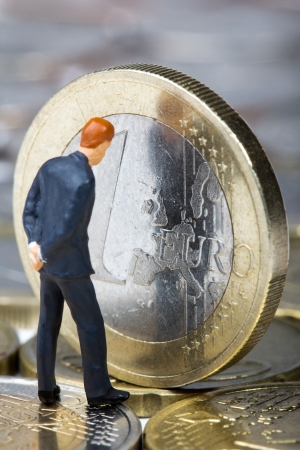 Figure of businessman looking on European Union on one euro coin