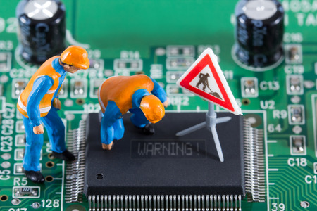 Miniature engineers fixing error on chip of circuit board  Computer repair concept  Close-up view  Stock Photo