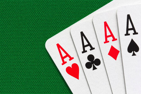Four aces over green textile background  Close-up view