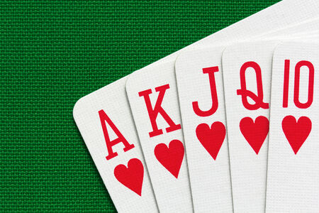 Royal flush over green textile background  Close-up view