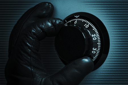 Hand of thief opens combination safe lock  Stock Photo