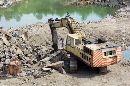 Track-type loader excavator machine doing earthmoving work at basalt quarry Stock Photo