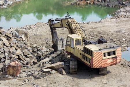 Track-type loader excavator machine doing earthmoving work at basalt quarry Stock Photo